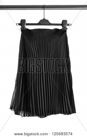 Elegant black pleated skirt on clothes rack isolated over white