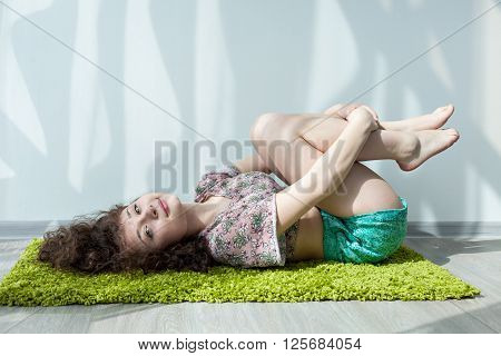 Young girl with curly hair lying on the floor, on the green carpet, do stretching exercises. Exercising in the morning in the bright sun room. Meditation. Practice yoga at home. Enjoy your life.
