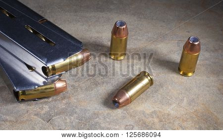 Ammunition with hollow point bullets and magazines for a handgun
