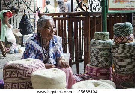 OAXACA MEXICO- MARCH 21, 2016: Woman smiles while selling his baskets, typical handicraft, in a market in Oaxaca, Mexico