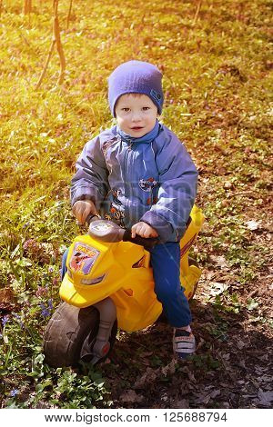Small boy playing outside with a yellow plastic toy motorbike