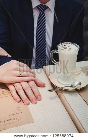 Loving woman hold man hand in her hands. Just married couple showing up wedding rings. Near Cup of latte coffee with chocolate on saucer with spoon stand on brown wooden table in cafe. Text on craft paper: singing jackpot punch... select one autobiography
