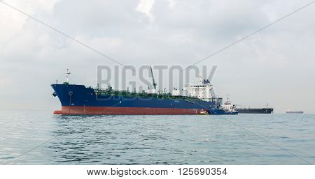 Blue ship is bunkering by small craft in the open sea