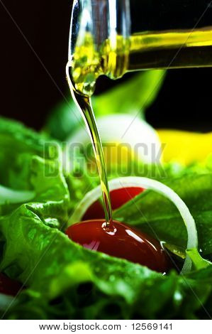 Healthy Salad and pouring olive oil closeup