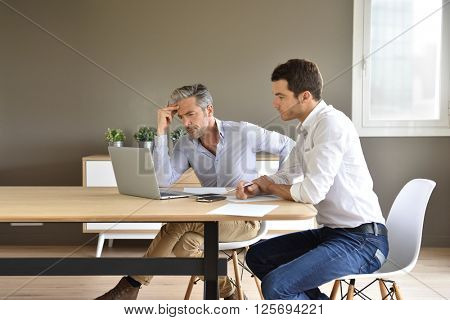 Businessmen working together in office with laptop