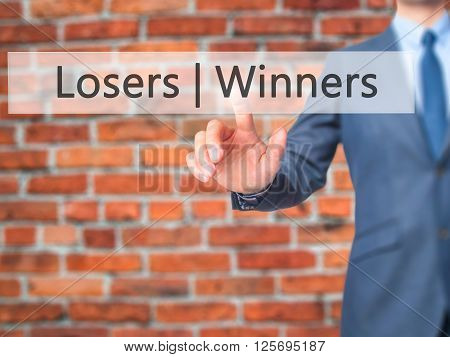 Winners  Losers - Businessman Hand Pressing Button On Touch Screen Interface.