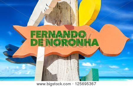 Fernando de Noronha signpost with beach background