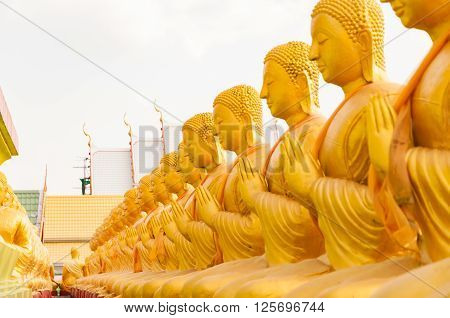 Row of golden bhudda statue in Nakorn Na Yok Thailand
