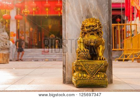 Golden chinese lion guardian sculpture in front of the gate to the temple