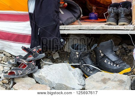 Composition with Variety of Boots Beach Sandals Heavy Mountain Plastic Boots Moderate Hiking Shoes All Dirty and Old