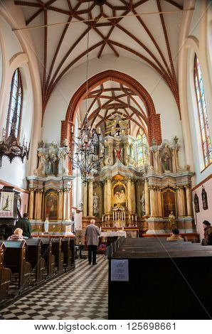 VILNIUS, LITHUANIA - OCTOBER 17, 2011: Interiors of Roman Catholic Church of St Anne - an example of Flamboyant Gothic and Brick Gothic styles. Beautiful altar and unidentified people