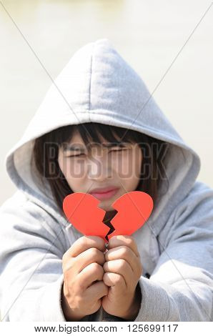 Sad Woman Seeing to Red Broken Heart on Hands