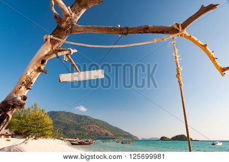 Dried dead tree with rope and a blank signage in front of a beach and blue sky