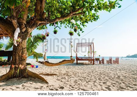 Swing hanging under a big tree for wedding ceremony decoration with pavilion and wedding arch on the beach