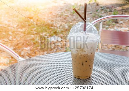 plastic glass of iced coffee capuchino on metal table with sun light above