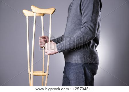 Man on crutches on a gray background. Studio shot