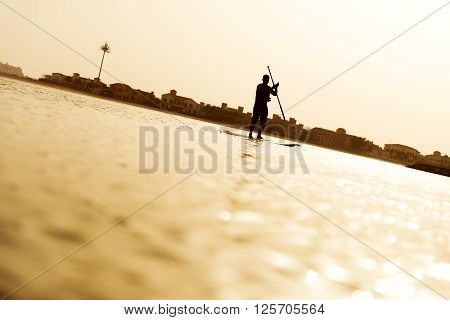 Silhouette of a man paddling board on the sunset.