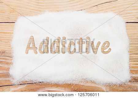 Close-up of sugar with text Addictive on weathered wood background