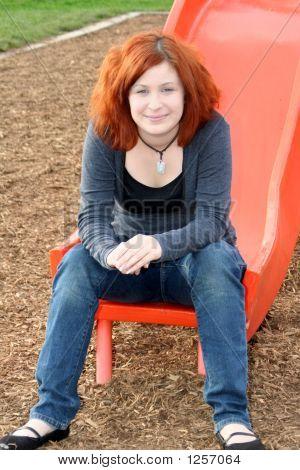 Smiling Teen Sitting On Sliding Board