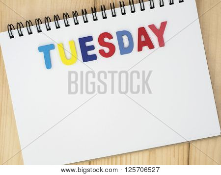 Tuesday word spell by wooden letters on blank notebook with wood background (Weekdays word series)