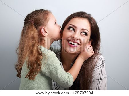 Happy Cute Kid Girl Whispering The Secret To Her Smiling Mother In Ear With Fun Face On Blue Backgro