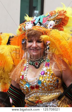 Cajamarca Peru - February 7 2016: Closeup of older woman in jeweled and feathered colorful costume marching in Carnival parade Cajamarca Peru on February 7 2016