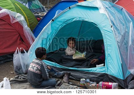 EIDOMENI, GREECE - MARCH 17, 2015: Two boys from Syria and their mother sit in their tent on March 17, 2015 in the refugee camp of Eidomeni, Greece. For several weeks more than 10.000 refugees and immigrants wait here for the borders to open.