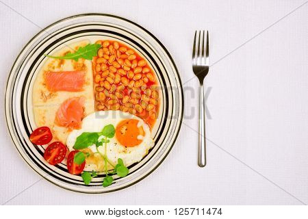 Breakfast plate with fried egg baked beans potato scones and smoked Scottish salmon from above