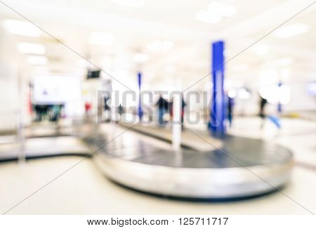 Abstract bokeh of conveyor belt at baggage claim sector area - Defocused background of international airport arrivals terminal gate - Travel concept and wanderlust business lifestyle