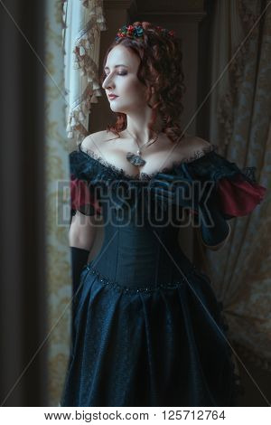Woman in Victorian dress standing at the window.