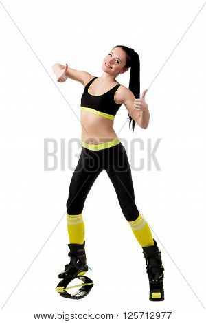 Smiling slender brunette girl with long hair in a black sportwear and kangoo jumps shoes showing a fingers up sign OK. isolated on white background in studio.