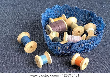 Knitted basket with coils colored sewing thread on fabric background.