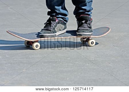 Close up of a skateboarders feet while skating on concrete at the skate park.
