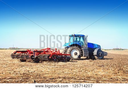 Blue tractor working in an open field on a sunny day