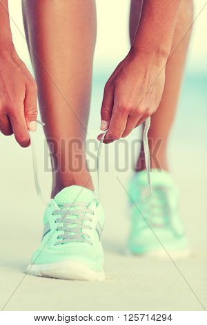 Active life runner girl tying running shoes laces. Healthy lifestyle woman runner tying running shoes laces for cardio training on beach at sunset. Female athlete exercising.