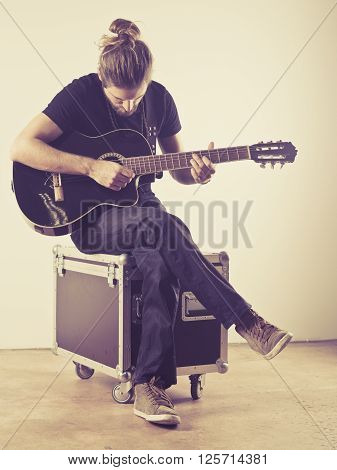 Photo of a young attractive man with long hair and beard sitting on a flight case and playing an acoustic guitar. Filtered to look vintage.