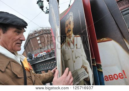 ST. PETERSBURG RUSSIA - MAY 1: Man with portrait of Soviet dictator Josef Stalin takes part in the May day demonstration in May 1 2010