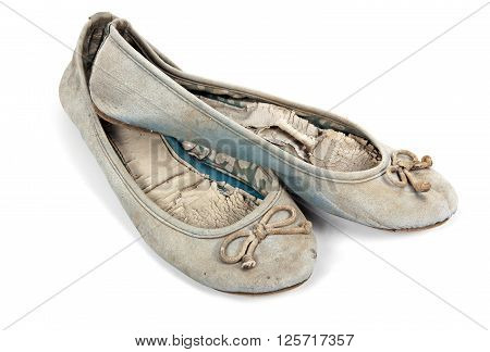 Pair of old well used blue tattered female worn-out shoes on white