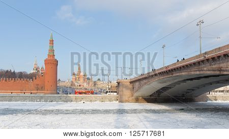 Moscow - January 7 2016: People walk by and large Moscow River bridge across the Moscow River and see the Kremlin and St. Basil's Cathedral in winter January 7 2016 Moscow Russia