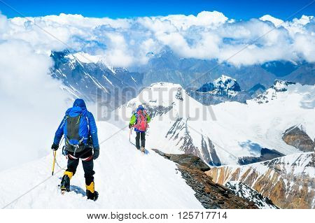Group of climbers reaches the top of mountain peak. Climbing and mountaineering sport. Teamwork concept.