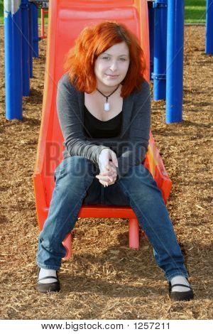 Teen Sitting On Sliding Board