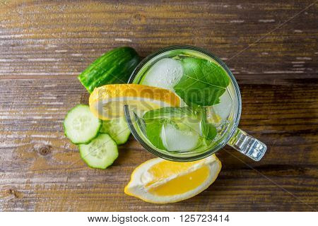 Glass of water on old wooden background