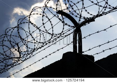 Dramatic Clouds Behind Barbed Wire Fence On A Prison Wall