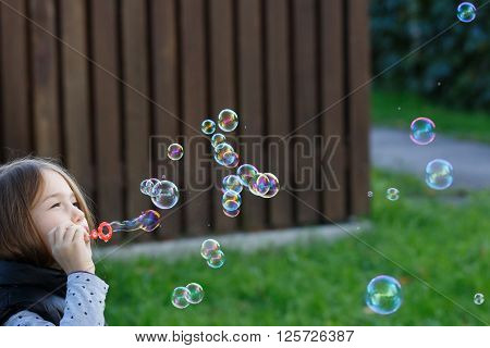 Little girl blowing bubbles having fun enjoying carefree childhood. Youth fun and children games concept with copy space.