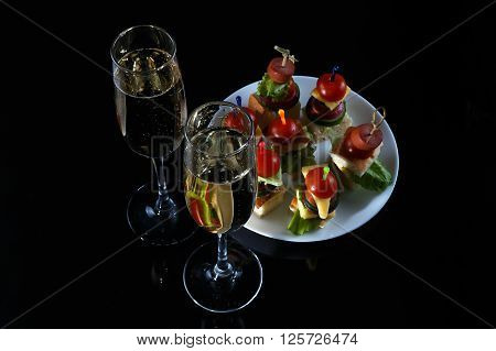 Small snacks canape with cherry tomatoes cheeze sausages and vegetables on bread on skewers on white plate with two glasses of champagne against rustic wooden background horizontal overhead view