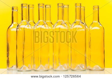 Ten empty glass transparent bottles standing in a row against yellow background