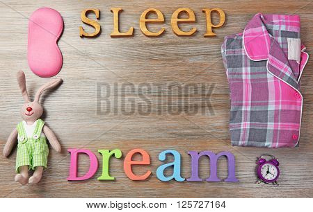 Insomnia concept with sleeping accessories on wooden table, top view