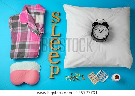 Insomnia concept. Sleeping accessories on blue background
