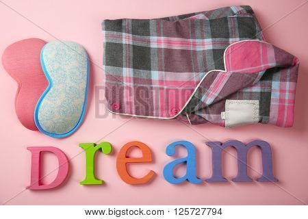 Word DREAM, sleeping masks and pajamas on pink background