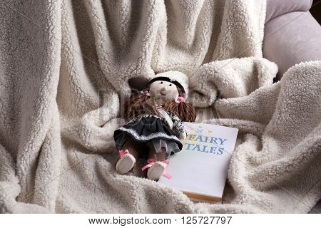 Rag doll with fairy tales book on  bedspread. Childhood concept